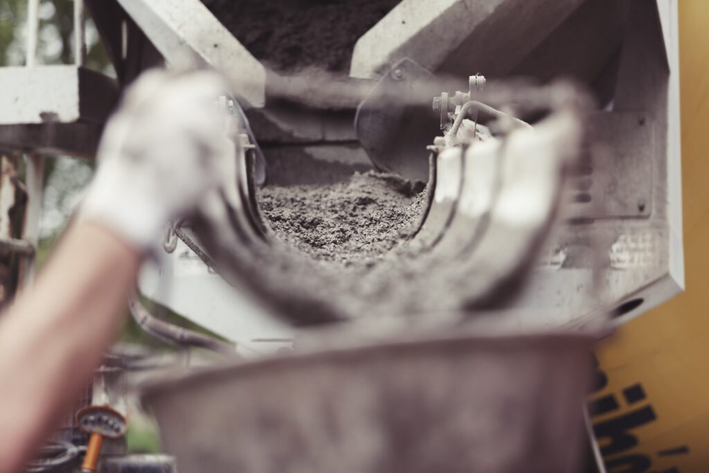 This picture shows the scene of a construction site. In the foreground a hand wearing work gloves is carrying a bucket. In the background a cement truck is visible. Cement is flowing from the truck into the bucket.